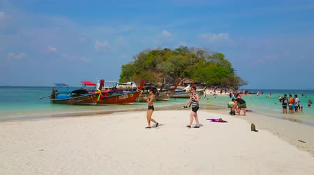 sziget : AO NANG, THAILAND - APRIL 26, 2019: The white sand shallow beach of Koh Mor Island with a view on moored longtail boats and small Koh Tup Island, covered with greenery, on April 26 in Ao Nang