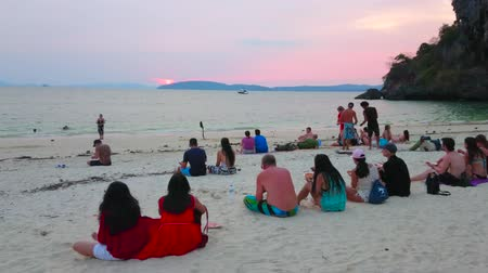 indianin : AO NANG, THAILAND - APRIL 26, 2019: The tourists watch sunset over the waters of Andaman sea, sitting on the Phra Nang beach of Railay (Rai Leh) Peninsula, on April 26 in Ao Nang Wideo