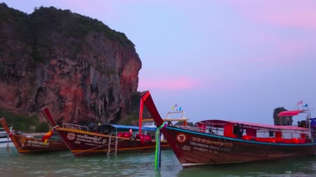 crepúsculo : AO NANG, THAILAND - APRIL 26, 2019: The wooden longtail boats with colorful ribbons and wreaths are moored at the twilight Phra Nang beach of Railay (Rai Leh) Peninsula, on April 26 in Ao Nang