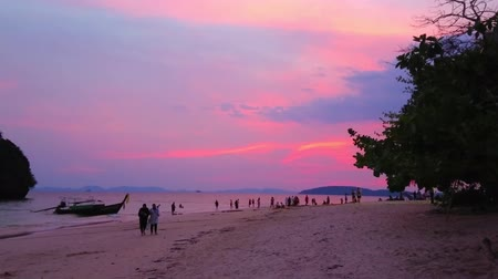 crepúsculo : AO NANG, THAILAND - APRIL 26, 2019: Romantic twilight walk through the Phra Nang beach of Railay (Rai Leh) Peninsula with a view on last sun rays and silhouettes of boats, on April 26 in Ao Nang