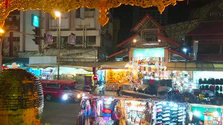 noc : CHIANG MAI, THAILAND - MAY 2, 2019: The view on pavilion of Kalare Night Market from the carved porch of Night Bazaar shopping center with fountain on the foreground, on May 2 in Chiang Mai Wideo