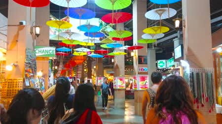noc : CHIANG MAI, THAILAND - MAY 2, 2019: The covered alleyway of Kalare Night Market is decorated with  colored Oriental umbrellas, hanging from the ceiling, on May 2 in Chiang Mai