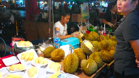 bakkaliye : CHIANG MAI, THAILAND - MAY 2, 2019: The street seller of Warorot Night Market cuts and packs durians, standing at the counter of tiny stall, on May 2 in Chiang Mai Stok Video