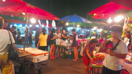 noc : CHIANG MAI, THAILAND - MAY 2, 2019: The fruit stalls of Warorot Night Market with bunches of lychee on branches and other tropical fruits, on May 2 in Chiang Mai