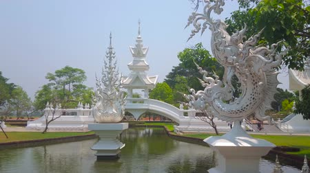 dekorasyon : CHIANG RAI, THAILAND - MAY 9, 2019: Enjoy the garden of White Temple (Wat Rong Khun) with a pond, fountains, bridges, ornate sculptures of Thai mytical creatures, on May 9 in Chiang Rai