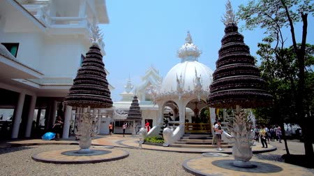 dekorasyon : CHIANG RAI, THAILAND - MAY 9, 2019: The carved shrine and prayer trees with numerous metal bo (pho, bodhi) silver leaves, located on the grounds of White Temple (Wat Rongkhun), on May 9 in Chiang Rai Stok Video