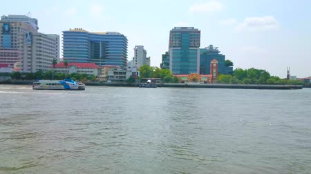 очки : BANGKOK, THAILAND - APRIL 22, 2019: Wide Chao Phraya river with boats, ferries and tourist ships floating in front of the modern glass buildings of offices and business centers, on April 22 in Bangkok Стоковые видеозаписи