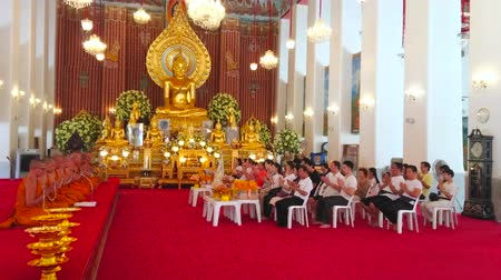 sziget : BANGKOK, THAILAND - APRIL 23, 2019: The Bhikkhu monks and Buddhist devotees on worship in richly decorated Ubosot of Wat Chana Songkhram monastery, on April 23 in Bangkok