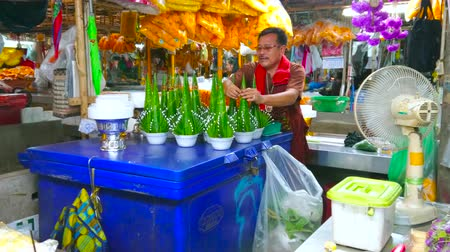 díszítés : BANGKOK, THAILAND - APRIL 23, 2019: The vendor of Pak Khlong Talat flower market makes compositions for Buddhist ritual offerings of banana leaves cones and jasmine flowers, on April 23 in Bangkok