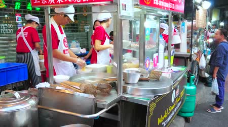 sudeste : BANGKOK, THAILAND - APRIL 23, 2019: The street food cart in busy Yaowarat road of Chinatown offers traditional Thai and Chinese noodle dishes, on April 23 in Bangkok