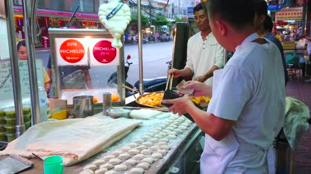 air vehicle : BANGKOK, THAILAND - APRIL 23, 2019: The roadside cafe in Yaowarat avenue in Chinatown with open air kitchen, where cooks prepare tasty deep fried bread sticks, on April 23 in Bangkok Stock Footage