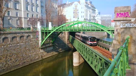 dworek : VIENNA, AUSTRIA - FEBRUARY 18, 2019: The trains run through the Zollamtsbrucke bridge above Wien River under pedestrian arched Zollamtssteg bridge, on February 18 in Vienna.