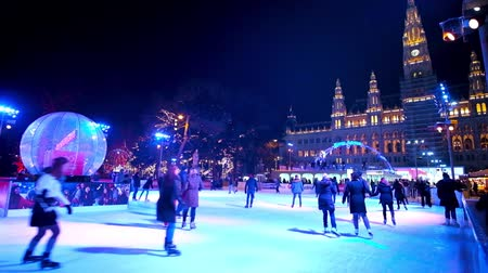historical : VIENNA, AUSTRIA - FEBRUARY 18, 2019: The crowded ice skating rink in front of brightly illuminated Town Hall (Rathaus), on February 18 in Vienna.