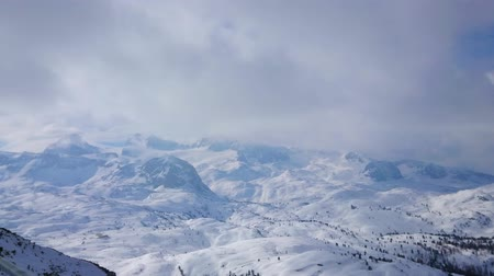 trilhas : Panorama of the snowbound Dachstein Alps with peaks, hidden in heavy clouds and fog, Salzkammergut, Austria.