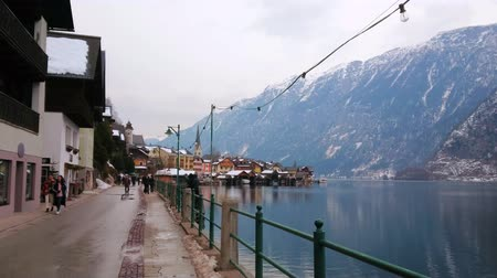 falu : HALLSTATT, AUSTRIA - FEBRUARY 21, 2019: Cloudy winter evening sky over the wet Seestrasse embankment of Hallstatter see (lake), on February 21 in Hallstatt Stock mozgókép