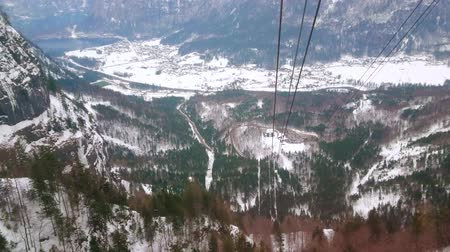 chmury : The air lift, riding down the steep slope of Krippenstein mount, overlooks Obertraun valley, rocky Alps of Dachstein massif and winter forests, Salzkammergut, Austria