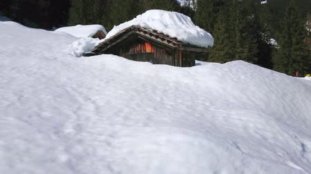 sníh : The deep snow covers highland valley in Dachstein Alps, the streams of melted snow drops down from the roof of the old wooden house, seen through the tall snowdrifts, Gosau, Austria