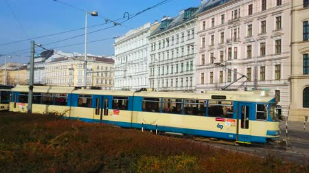 dworek : VIENNA, AUSTRIA - FEBRUARY 18, 2019: The vintage blue-white tram rides along the Resselpark and crosses busy avenue, lined with classical edifices, on February 18 in Vienna.