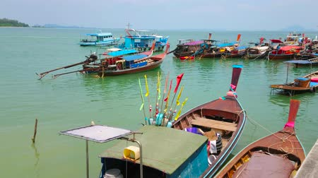 украшенный : AO NANG, THAILAND - APRIL 26, 2019: The numerous old wooden longtail boats, decorated with colorful ribbons and flowers are docked at Ao Nammao Pier, on April 26 in Ao Nang Стоковые видеозаписи