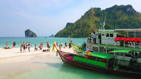 sziget : AO NANG, THAILAND - APRIL 26, 2019: The crowded sand spit amid the shallow beach between Koh Mor and Koh Tup Islands with moored tourist ships and longtail boats, on April 26 in Ao Nang