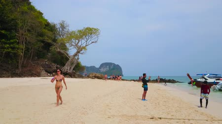 turisták : AO NANG, THAILAND - APRIL 27, 2019: The tourists relax, swim and make pictures on sandy beach of  Ko Mai Phai (Bamboo Island), on April 27 in Ao Nang