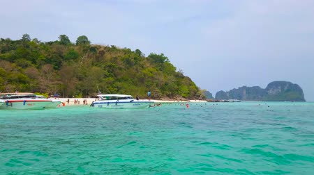 sziget : AO NANG, THAILAND - APRIL 27, 2019: The coast of  Ko Mai Phai (Bamboo Island) with moored speed boats, numerous tourists, lush bamboo greenery and emerald waters of Andaman sea, on April 27 in Ao Nang Stock mozgókép