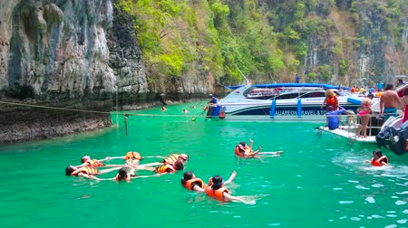 laguna : PHIPHI LEH, THAILAND - APRIL 27, 2019: The group of tourists performs the figures of synchronized swimming in Pileh Bay lagoon of Phi Phi Leh Island, on April 27 in PhiPhi Leh