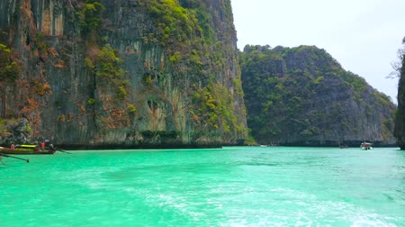 águas : PHIPHI LEH THAILAND - APRIL 27, 2019: The old longtail boats are bobbing on the clear emerald waters of Pileh Bay lagoon, popular among tourists, snorkellers and swimmers, on April 27 on PhiPhi Leh