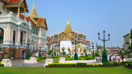 dworek : BANGKOK, THAILAND - MAY 12, 2019: Vintage streetlights, flower beds and green lawn at the Chakri Maha Prasat Throne Hall and Phra Thinang Dusit Maha Prasat Hall (on background), on May 12 in Bangkok