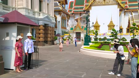 turisták : BANGKOK, THAILAND - MAY 12, 2019: Tourists makes pictures with Thai Royal Honor Guard soldier on sentry duty in front of the Chakri Maha Prasat Throne Hall of Grand Palace, on May 12 in Bangkok