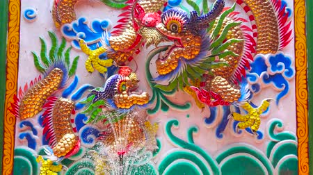 histórico : BANGKOK, THAILAND - MAY 12, 2019: The stucco panel with relief colorful dragons in front of the fountain in courtyard of Lao Pun Tao Kong Shrine, located in Chinatown, on May 12 in Bangkok