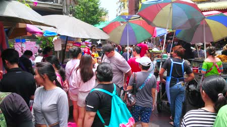 получать : BANGKOK, THAILAND - MAY 12, 2019:  Visitors and food sellers with carts get stucked in Sampeng Lane market (Soi Wanit alley) of Chinatown to skip the car, driving in Mangkon Road, on May 12 in Bangkok Стоковые видеозаписи
