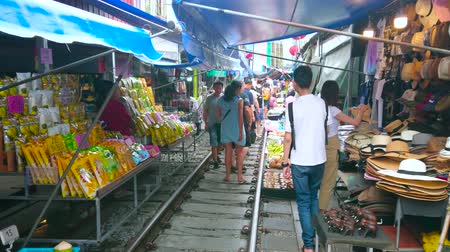 romênia : MAEKLONG, THAILAND - MAY 13, 2019: Tourists walk the railroad and make shopping in stalls of Maeklong Railway Market - the popular tourist spot in country, on May 13 in Maeklong