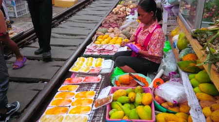 comerciante : MAEKLONG, THAILAND - MAY 13, 2019: Maeklong Railway Market fruit stall merchant packs the slices of papaya and mango to the plastic containers, sitting by the railroad, on May 13 in Maeklong