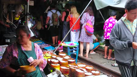 comerciante : MAEKLONG, THAILAND - MAY 13, 2019: The vendor of the small stall in Maeklong Railway Market sells the salted fish in bamboo cages - the popular Thai dish, on May 13 in Maeklong