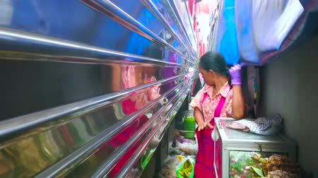 maeklong : MAEKLONG, THAILAND - MAY 13, 2019: The elderly vendor is leaning against the wall at the fruit stall, while the train is riding through the Maeklong Railway Market, on May 13 in Maeklong
