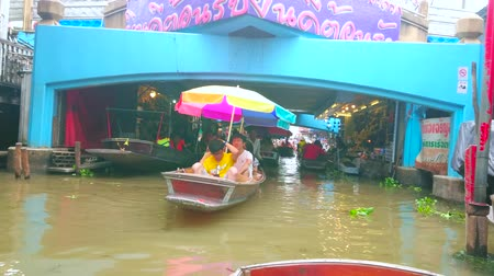 都市景観 : DAMNOEN SADUAK, THAILAND - MAY 13, 2019: Tourist boats float to the passage with souvenir stalls, located under the bridge of Ton Khem floating market, on May 13 in Damnoen Saduak