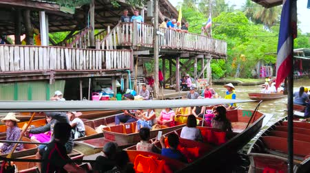 comerciante : DAMNOEN SADUAK, THAILAND - MAY 13, 2019: High activity of boats, floating through the narrow canal (klong) of Ton Khem floating market, lined with stall, shops and cafes, on May 13 in Damnoen Saduak