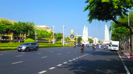 semt : BANGKOK, THAILAND - APRIL 24, 2019: The fast traffic through the Ratchadamnoen Avenue, lined with lush trees, overlooking Democracy Monument on background, on April 24 in Bangkok Stok Video