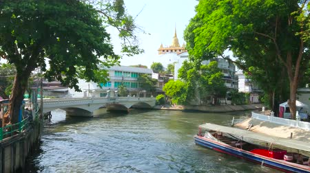паром : BANGKOK, THAILAND - APRIL 24, 2019: The long ferry makes complex maneuvers to turn around in tight space of Maha Nak Khlong (canal), passing by the Golden Mount Temple, on April 24 in Bangkok Стоковые видеозаписи