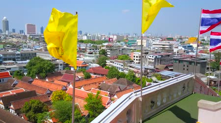 residencial : BANGKOK, THAILAND - APRIL 24, 2019: The bright yellow Royal Flags are waving on the wind on the upper platform of the Wat Saket (Golden Mount) temple, on April 24 in Bangkok