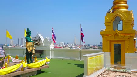 pom : BANGKOK, THAILAND - APRIL 24, 2019: The view on city skyline with waving flags from the small walking platform around Chedi on the top of Wat Saket (Golden Mount) Temple, on April 24 in Bangkok