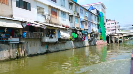 residencial : BANGKOK, THAILAND - APRIL 24, 2019: The boat trip through the Bang Lamphu Khlong is best way to explore old town with many small bridges, shabby houses and greenery, on April 24 in Bangkok