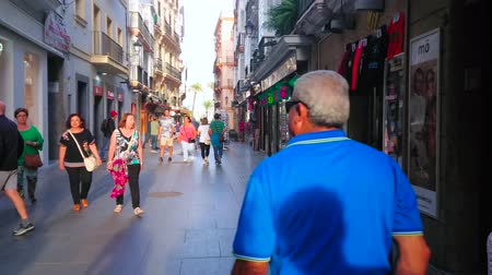 CADIZ, SPAIN - SEPTEMBER 19, 2019: The day walk through the crowded shopping Pelota street, located between Cathedral and San Juan de Dios square, on September 19 in Cadiz Stock Footage