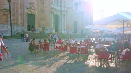 torre : CADIZ, SPAIN - SEPTEMBER 19, 2019: The crowded summer terrace of the restaurant in Plaza de la Catedral square in front of the old Cathedral, on September 19 in Cadiz