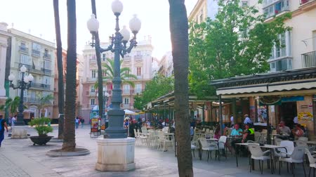 kostel : CADIZ, SPAIN - SEPTEMBER 19, 2019: The vintage streetlight in Plaza de San Juan de Dios square with outdoor cafes, palm trees and Pazos Miranda House on background, on September 19 in Cadiz