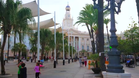 torre : CADIZ, SPAIN - SEPTEMBER 19, 2019: The large pedestrian Plaza de San Juan de Dios, the central walking sqaure in old town with Town Hall, palm alley and white sunshades, on September 19 in Cadiz Stock Footage