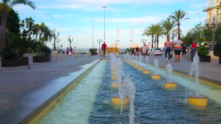 dworek : CADIZ, SPAIN - SEPTEMBER 19, 2019: Relax at the fountains in San Juan de Dios square with a view on the gate of port with old white Pillars of Hercules, on September 19 in Cadiz Wideo
