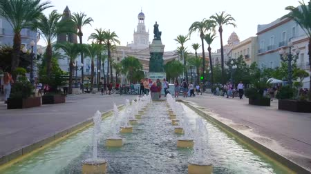 torre : CADIZ, SPAIN - SEPTEMBER 19, 2019: Explore San Juan de Dios square with tall palms, plants in pots, fountains, Moret statue, cafes and Town Hall building, on September 19 in Cadiz