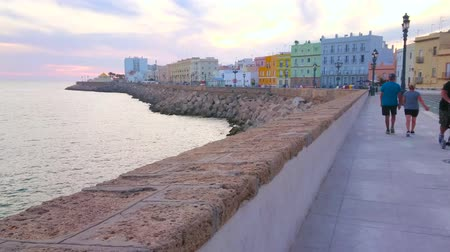crepúsculo : CADIZ, SPAIN - SEPTEMBER 19, 2019: Campo del Sur avenue is nice place for evening walk with a view on Atlantic Ocean, colorful old buildings, bastions of the fortress, on September 19 in Cadiz